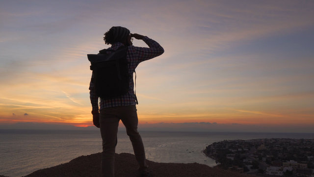 handsome middle eastern male standing on a cliff and looking ahead