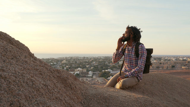 Adult african male smoking joint with cannabis sitting on a cliff at sunrise