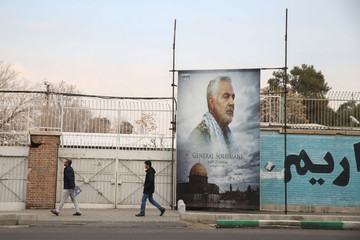 People walk past a picture of Iranian Major-General Qassem Soleimani, head of the elite Quds Force, who was killed in an air strike at Baghdad airport, as it is seen in front of the former U.S. Embassy's building in Tehran