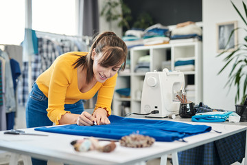 Charming caucasian smiling dedicated seamstress drawing  seam with chalk on a skirt.