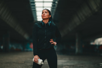 Young woman in black sportswear under overpasses resting after jogging in cold weather holding protein shake