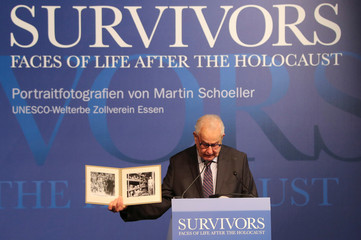 Holocaust survivor Naftali Fuerst shows pictures at the opening of a photography exhibition in Essen