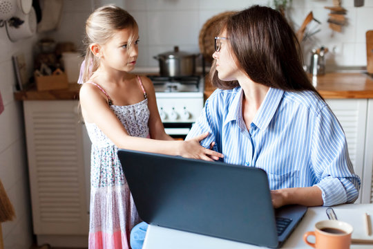 Working mother in home office. Woman and child girl using laptop. Daughter needs attention from irritated, exhausted, stressed mom. Freelancer workplace in kitchen. Female business. Lifestyle moment.