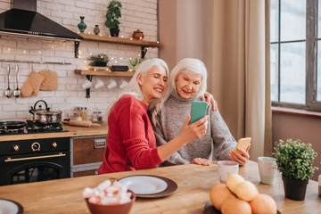 Two mature grey-haired positive ladies making pictures