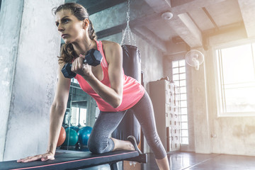Woman lifting dumbbell on the bench. Gym workout and training concept.