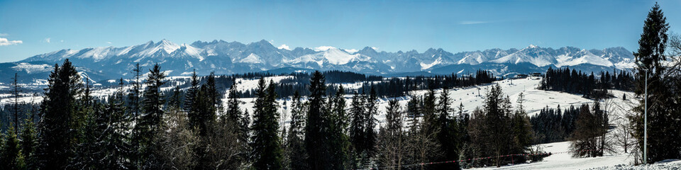 Fotobehang Blauw Wide panorama of Tatra mountains in winter, viewed from Bania mountain in Bialka ski resort with ski chair lift. Far view of Kasprowy Wierch, main Tatra ski slope in Poland in the very middle