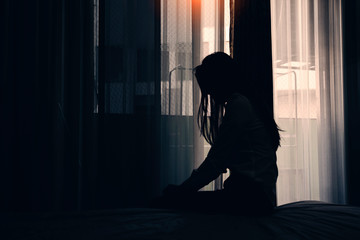 Sad young woman sitting on the bed in the bedroom, People with depression concept.