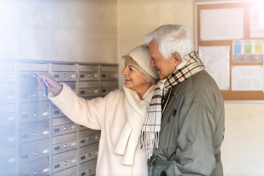 Senior couple unlocking apartment mailbox