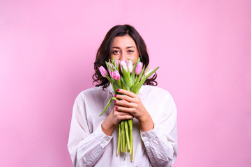 Studio portrait of gorgeous young brunette woman with long wavy hair wearing white loose cotton shirt, holding bouquet of tulip flowers. Pink isolated background, copy space, close up.