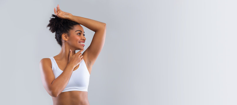Cheerful black girl smelling her armpit over grey background