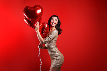 Portrait of young brunette woman posing with helium inflated air balloons. Happy valentine's day concept. Joyful female with wavy hair over colorful background. Close up, copy space for text.