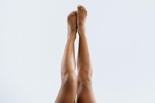 Beautiful afro woman lifting her legs up in air