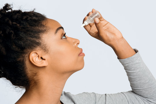 Young woman applying ophthalmology eyedropper, glaucoma eye prevention