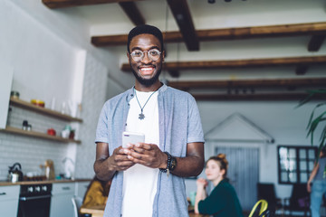 Content smiled African American man using smartphone at home