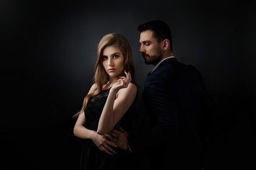 elegant couple on black background. handsome man and beautiful woman in black dress Wall mural