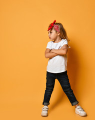 Cute kid blonde girl in a white t-shirt and a red bandage on her head is looking with her hands crossed at copy space