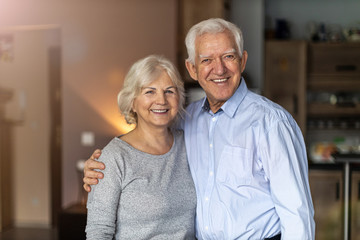 Happy senior couple embracing in their home