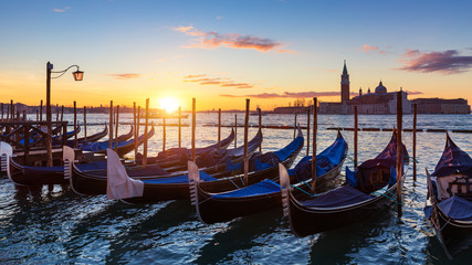Wall Murals Gondolas Venice with famous gondolas at sunrise, Italy. Gondolas in lagoon of Venice on sunrise, Italy. Venice with gondolas on Grand Canal against San Giorgio Maggiore church.