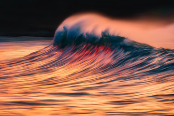 wave with spray breaking at sunset with in camera panning technique