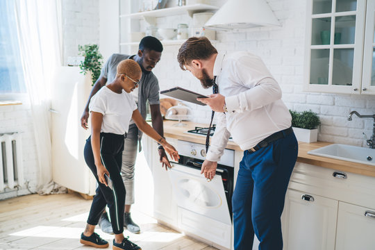 Confident estate agent showing kitchen to African American thoughtful couple