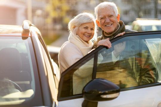 Happy senior couple with their new car