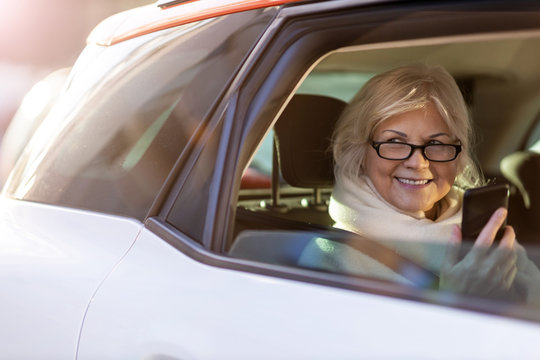 Senior woman with smartphone on the back seat of a car