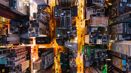 Fotomurales - Aerial top view of downtown district  buildings in night city light. Bird's eye view from drone of cityscape metropolis infrastructure, crossing streets with parked cars. Development infrastructure