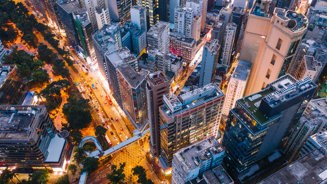 Aerial top view of downtown district  buildings in night city light. Bird's eye view from drone of cityscape metropolis infrastructure, crossing streets with parked cars. Development infrastructure