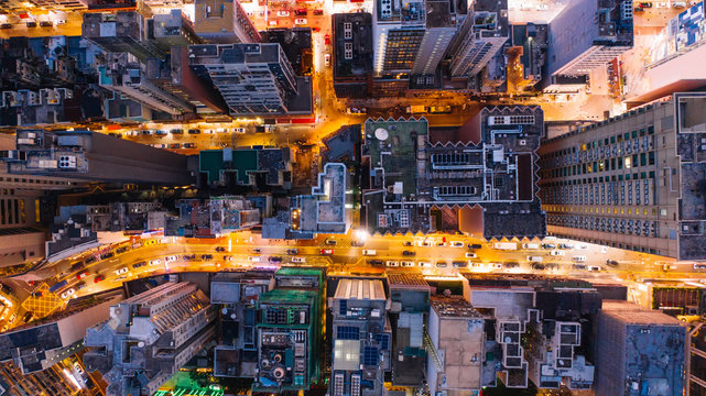Aerial top view of downtown district  buildings in night city light. Bird's eye view from drone of cityscape metropolis skyline, crossing streets with parked cars. Development infrastructure