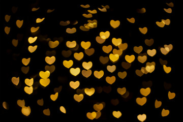 Abstract beautiful romantic picture of blur bright Gold-Yellow colored of swirl heart shaped bokeh on black from ornamental lights flickering. Background for Valentine's day or Love or Romance concept