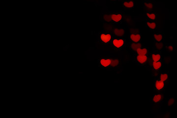 Abstract beautiful romantic picture of blur brightness red colored of swirling heart shaped bokeh on black from ornamental lights flickering. Background for Valentine's day or Love or Romance concept.