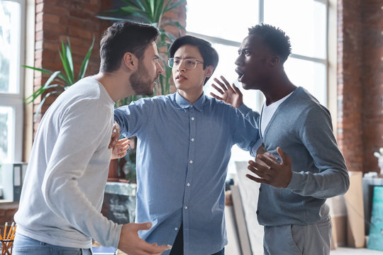 Young angry coworkers having quarrel at office