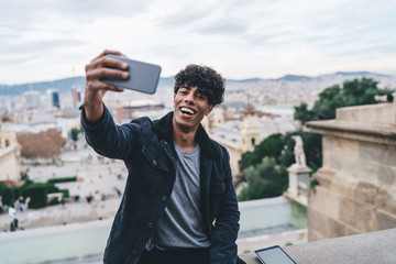 Portrait of excited Latino male tourist resting during Spanish holidays in Barcelona making selfie pictures on Montjuic area, happy emotional man photographing himself with cityscape on background