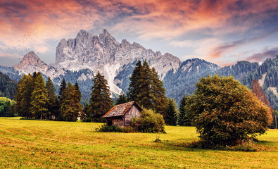 Awesome alpine highlands during sunset. Scenic image of fairy-tale Landscape with colorful sky and majestic Rock Mountain on background. Wild area. Amazing countryside in alps with traditional hut