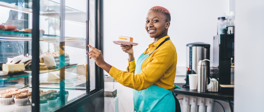 Shop assistant pointing at cake in pastry shop