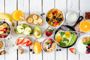 Healthy breakfast table scene with fruits, yogurts, oatmeal, cereal, smoothie bowl, nutritious toasts and egg skillet. Top view over a white wood background.