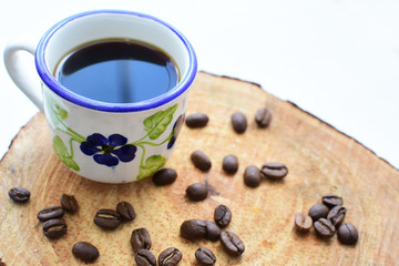 Traditional Colombian coffee cup and coffee beans on wooden background