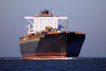 schwarzes Containerschiff von vorne