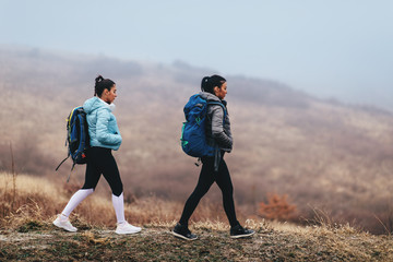 Two young women hikers during a cold day on the mountain