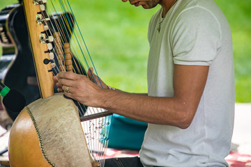 Fototapeta Midsection of male artist in white t-shirt performing traditional wooden harp kora while sitting during event in city against lawn obraz