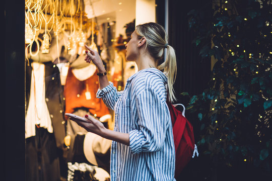 Woman with backpack pointing to shop window