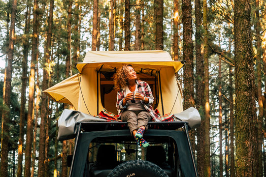 Travel and wanderlust lifestyle concept with happy lonely adult woman sit down on the roof tent car vehicle with wood forest in background enjoying nature and outdoors vacation
