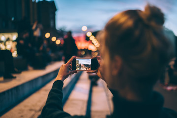 Back view of female generation photographing city urban setting during journey getaway connected to 4g wireless for sharing pictures to social media website, millennial woman taking images via camera