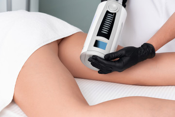 cosmetologist in rubber gloves doing endospheres therapy on female hips