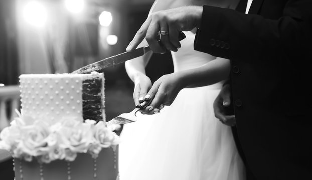 Black and white photo of couple hands cutting wedding cake. Happy bride and a groom is cutting their beautiful wedding cake on wedding banquet. Wedding and celebration concept.