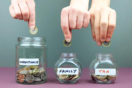 Hands putting in to different money jars. Spreading your inheritance money around concept.