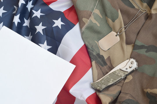 Army dog tag token and knife lies on Old Camouflage uniform and folded United States Flag