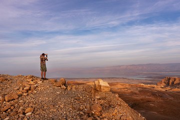 Tourist taking picture with the phone of the Masada fortress with the Dead sea on the background. Israel.