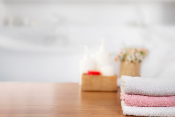 Towels on wooden top table with copy space on blurred bathroom background.