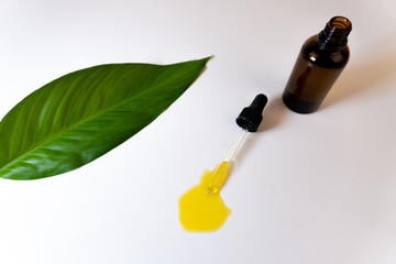 Top view of a bottle with CBD oil or any other essential oil and a green leaf on white background